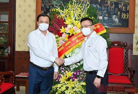Bí thư Thành ủy Hà Nội Đinh Tiến Dũng chúc mừng Tổng Biên tập Lê Quốc Minh.