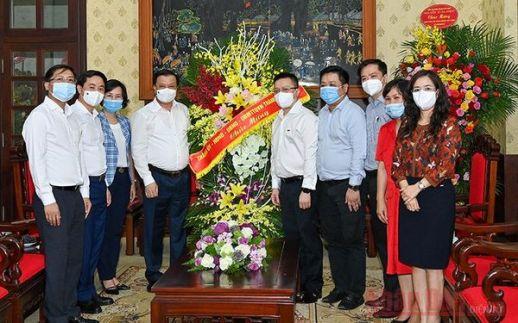 Đồng chí Đinh Tiến Dũng, Ủy viên Bộ Chính trị, Bí thư Thành ủy Hà Nội cùng các đồng chí lãnh đạo thành phố tặng hoa chúc mừng Báo Nhân Dân.