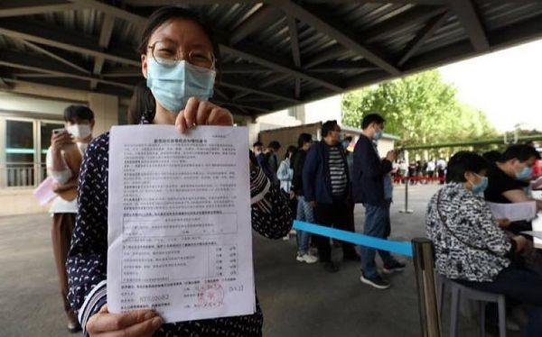 Một người dân Trung Quốc với giấy đăng ký mũi tiêm vaccine ngừa Covid-19 thứ nhất